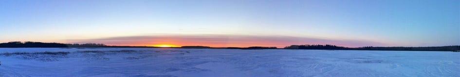 Puesta del sol en un lago congelado del invierno imagen de archivo