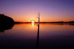 Puesta del sol en un lago del verano visto a través de un anillo de la caña de pescar Fotografía de archivo libre de regalías