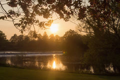 Puesta del sol en un parque sobre la mirada de un lago Imagenes de archivo