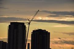 Puesta del sol en una grúa de construcción y dos torres de la propiedad horizontal Imagen de archivo