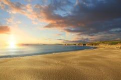 Puesta del sol en una playa aislada Foto de archivo libre de regalías