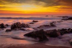 Puesta del sol en una playa con las rocas en agua en Portugal fotos de archivo libres de regalías