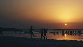 Puesta del sol en una playa ocupada con las porciones de gente Ubicación Dubai United Arab Emirates metrajes
