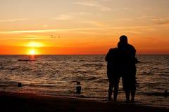 Puesta del sol en una playa - quiera la silueta de los pares Fotos de archivo libres de regalías