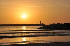 Puesta del sol entre el faro dos en la entrada del puerto deportivo Fotografía de archivo