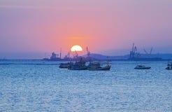 Puesta del sol entre los barcos del pescador fotos de archivo