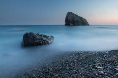 Puesta del sol escénica en una costa rocosa en la exposición larga Fotos de archivo libres de regalías