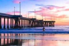 Puesta del sol espectacular con las personas que practica surf en la playa de Venecia Fotos de archivo