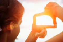 puesta del sol excesiva distante de la opinión de la mano que enmarca fotos de archivo