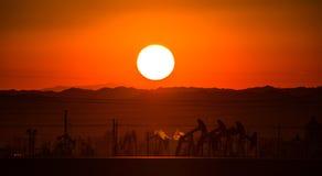 Puesta del sol, extractor del petro en frente Foto de archivo libre de regalías