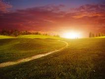 Puesta del sol fantástica sobre las colinas verdes del verano Fotografía de archivo libre de regalías