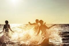 Puesta del sol feliz de la diversión de la playa de los amigos Imagen de archivo