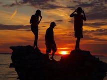 Puesta del sol - figuras de la silueta Imagenes de archivo