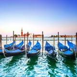 Puesta del sol, góndolas o gondole e iglesia de Venecia en fondo. Italia Imagenes de archivo