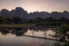 Puesta del sol gloriosa sobre las montañas que dominan Vang Vieng que pasa por alto el río de Nam Song y el puente de madera, Lao imagenes de archivo