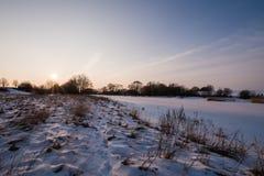 Puesta del sol hermosa cerca del río congelado Fotos de archivo