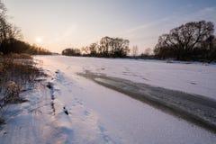Puesta del sol hermosa cerca del río congelado Fotografía de archivo libre de regalías