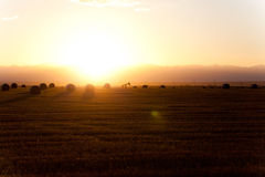 Puesta del sol hermosa con algunas balas de heno Fotos de archivo libres de regalías