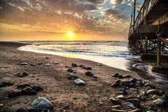 Puesta del sol hermosa con algunas rocas en la tierra delantera en Perú Foto de archivo