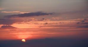 Puesta del sol hermosa con el avión de aterrizaje Foto de archivo libre de regalías