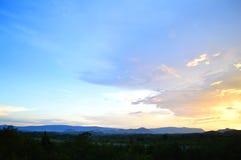 Puesta del sol hermosa con el cielo anaranjado nublado Foto de archivo