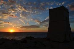 Puesta del sol hermosa con la torre histórica de Ein Tuffeiha al noroeste de Malta Fotos de archivo