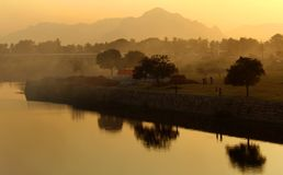 Puesta del sol hermosa con los árboles lago, fondo de la naturaleza de las colinas Foto de archivo