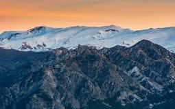 Puesta del sol hermosa con tonos anaranjados en el cielo y la cordillera coronada de nieve de Sierra Nevada imágenes de archivo libres de regalías