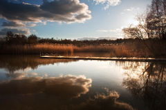 Puesta del sol hermosa de la última tarde sobre el embarcadero en el lago Fotos de archivo libres de regalías