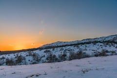 Puesta del sol hermosa de la montaña del invierno con un cielo anaranjado impresionante Rusia, Stary Krym Fotos de archivo