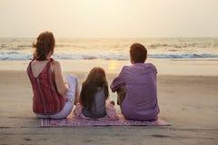 Puesta del sol hermosa de la reunión asiática de la familia sobre el mar con el niño imagen de archivo