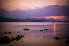 Puesta del sol hermosa en el mar con las montañas Fotografía de archivo libre de regalías