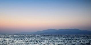 Puesta del sol hermosa en el mar y la montaña Imagen de archivo libre de regalías