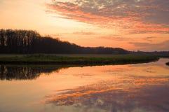 Puesta del sol hermosa en el prado con una gran reflexión del agua Imágenes de archivo libres de regalías
