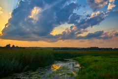 Puesta del sol hermosa en el río debajo del cielo nublado foto de archivo