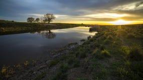 Puesta del sol hermosa en el río en el pueblo Imagen de archivo