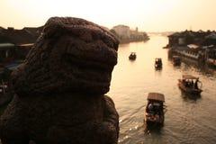 Puesta del sol hermosa en la ciudad antigua de Zhujiajiao, China Escultura china tradicional del león, naves en el agua, río imagen de archivo libre de regalías