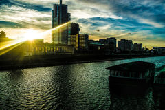 Puesta del sol hermosa en la ciudad en la orilla Imagen de archivo libre de regalías