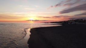 Puesta del sol hermosa en la costa romana en Ostia Lido con el mar tranquilo, reflexiones en el cielo espectacular del agua y una almacen de metraje de vídeo