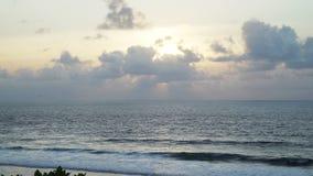Puesta del sol hermosa en la playa, haz luminoso que brilla a través del cloudscape Bali Indonesia metrajes