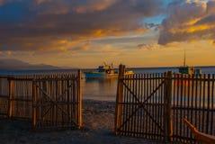 Puesta del sol hermosa en la playa La cerca sube en el fondo de las naves y del mar Pandan, Panay, Filipinas Fotografía de archivo libre de regalías
