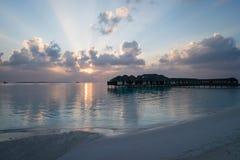 Puesta del sol hermosa en la playa que pasa por alto las casas de planta baja del agua en Maldivas fotografía de archivo libre de regalías