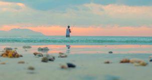 Puesta del sol hermosa en las zonas tropicales en el fondo de un pescador Who Fishes en el giro en el océano Pesca del pescador metrajes