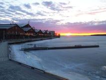 Puesta del sol hermosa en Lulea con hielo y casas imagen de archivo