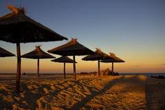 Puesta del sol hermosa en una playa arenosa hermosa con las sombrillas Paraguas de la paja en una playa tropical hermosa Panorama foto de archivo