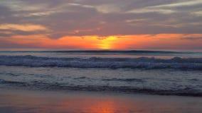 Puesta del sol hermosa en una playa con las ondas tranquilas almacen de video