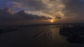Puesta del sol hermosa, imponente sobre el agua, sobre los barcos en un muelle o un puerto de mirada industrial foto de archivo