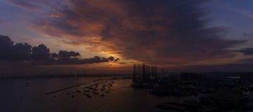 Puesta del sol hermosa, imponente sobre el agua, sobre los barcos en un muelle o un puerto de mirada industrial fotos de archivo libres de regalías