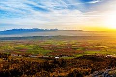 Puesta del sol hermosa sobre campos agricultiral coloreados Foto de archivo