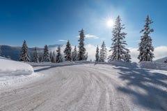 Puesta del sol hermosa sobre el camino nevoso Fotografía de archivo
